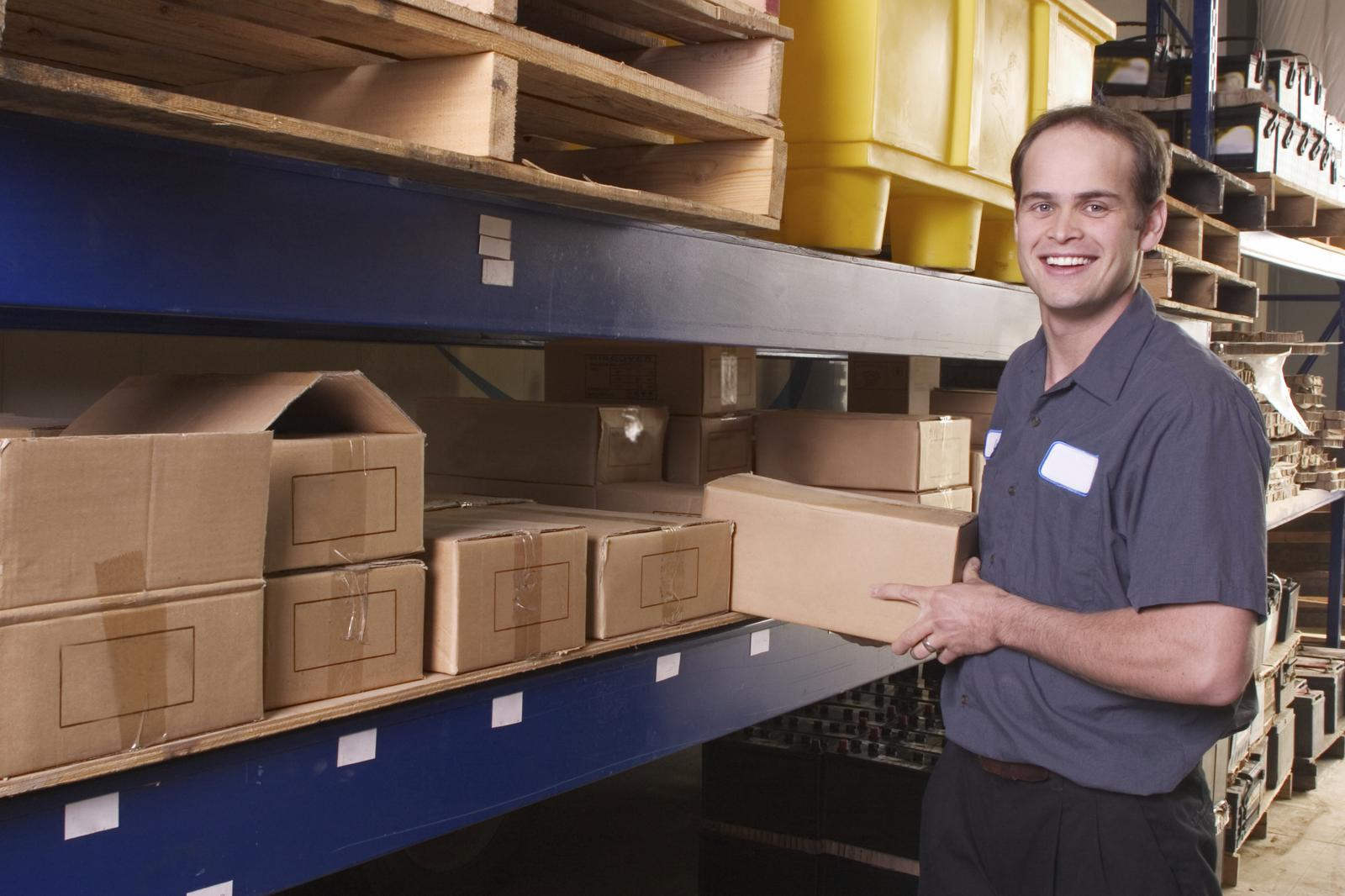 Smiling service worker in standing next to shelves of packages